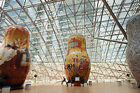 Moscow, Russia, 15/06/2011..People sit among an exhibition of of giant Russian matryoshki, or nesting dolls, in the newly-opened Afimall shopping centre. The dolls, designed by Boris Krasnov, are from 6 to 13 metres high, and each is decorated in a different style of traditional Russian folk art..Left - right: Fedoskono, Gorodetskaya  and Vologodskoe lacework styles.