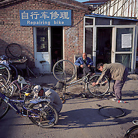Chinese workers repair bicycles outside a bike shop   at a village on the outskirts of Beijing, China in November, 2010. (Mamiya 6, 75mm f3.5, Kodak Ektar 100 film)