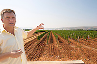 The vineyard with vines on the plain near Mostar with the mountain range in the background. The vineyard manager UNK UNK. Looking out over his vast vineyards. Vranac grape variety. Typical red reddish clay sand sandy soil mixed with pebbles rocks stones in varying amount. Vineyard on the plain near Mostar city. Hercegovina Vino, Mostar. Federation Bosne i Hercegovine. Bosnia Herzegovina, Europe.