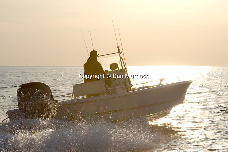 A center console fishing boat heading into the sunrise