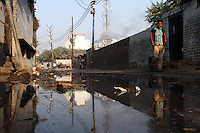 A local man walks along a street that has been flooded by industrial waste water from a nearby leather tannery.