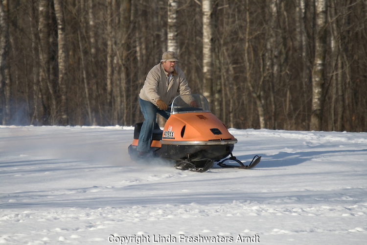 Man driving vintage 1970 AMF Mark V 400 Ski-Daddler snowmobile without helmet