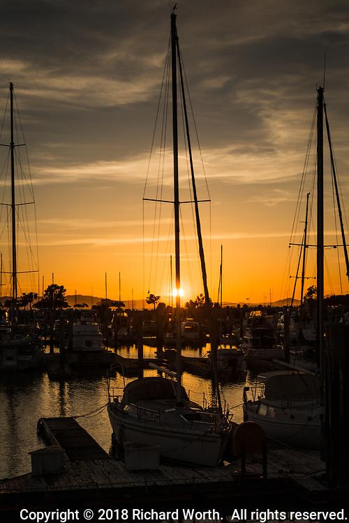 The setting sun is partially hidden by a sailboat mast at the San Leandro Marina on San Francisco Bay.