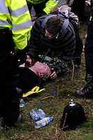 A police officer injured in clashes with climate activists taking direct action against the coal fired power station at Ratcliffe on Soar, south of Nottingham, is assisted by a medically trained protester. The power station, owned by E.ON, is the third largest emitter of greenhouse gases in the UK.