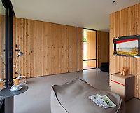 A guest room is furnished with a grey canvas pouffe and the walls are lined with pine cladding
