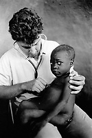 """Mozambique. Province of Tete. Cazula is a small village in the bush. A white doctor (expatriate) with his stethoscope listens to the lungs of a young boy , who sits on the doctor's thighs. Medical consultation. The village can only be reached by plane. Beacause of the war between the Government and the rebel of the Frelimo party, the roads are either mined or too dangerous to travel on. The airplane is part of the  """"Flying Doctors"""" programm ran by the non governmental organisation (ngo) Médecins Sans Frontières (MSF) of Belgium.  © 1992 Didier Ruef"""