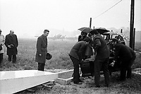 21 avril 1972. Au 1er plan, vue de dos de 3 hommes transportant le cercueil de Didier Daurat vers le caveau ; au 2nd plan vue de face de la famille et des amis autour du caveau, parapluies ; en arrière-plan avions sur la piste de Montaudran, brouillard, pluie. Cliché pris lors de la cérémonie organisée dans le cadre du transfert du corps de Didier Daurat dans un caveau en bordure de la piste de Montaudran.