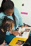 Preschool 3-4 year olds female teacher reads book to girl in classroom