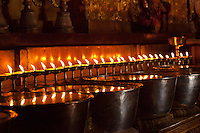 Candles reflect in bowls of molten butter left as an offering inside a buddhist temple within Tashilhunpo monastary