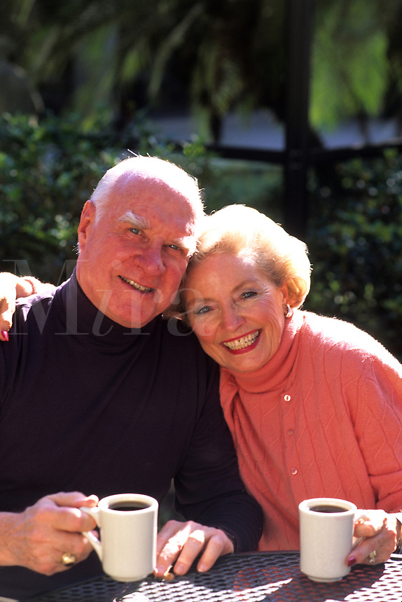 Healthy retired couple in her 70s having coffe