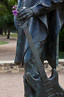 Stevie Ray Vaughan SRV Statue and colorful flowers in hand in Austin, Texas