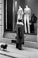 Milano, via Montenapoleone. Una donna con un cane osserva i capi in vetrina alla boutique di Valentino --- Milan, Montenapoleone street. A woman with a dog looks at the articles of clothing at the shop window of Valentino's boutique