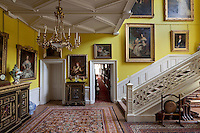 An array of family portraits lines the stair hall. The yellow wall colour was chosen by the present duke's mother