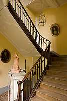 A simple wooden staircase with a metal balustrade ascends to the first floor