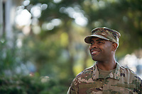 Young man in Army or Airforce uniform outside in natural light.