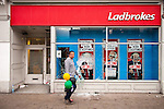 © Joel Goodman - 07973 332324 . 07/08/2011 . London , UK . A man walks outside a vandalised branch of Ladbrokes . Overnight rioting and looting in Tottenham , following a protest against the police shooting of Mark Duggan . Photo credit : Joel Goodman