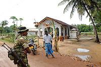 SRI LANKA, Trincomalee, tamil refugees are kept by the singhalese government fter the war against the LTTE Tamil Tigers in so called welfare camps in remoted jungle areas , the camps are under total control of Sri Lankan army, tamil Hindu temple and armed singhalese soldier / SRI LANKA Trincomalee, Tamilen werden nach dem Krieg der singhalesischen Armee und Regierung gegen die LTTE Tamil Tiger in sogenannten welfare camps in abgelegenen Dschungelgebieten interniert , umgesiedelt und als Menschen 2. Klasse behandelt, die camps sind durch Militaerposten und Armeelager umgeben , urspruengliche Tamilengebiete werden mit Singhalesen besiedelt, tamilischer Hindutempel und singhalesischer Soldat mit Waffe