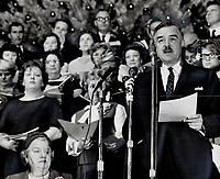Ontario Premier John Robarts gives the Christmas greeting before a choir of 50 civil servants presented Yuletide music at the Parliament buildings today. The program was the first of four presentations of carols the choir will give on the stairway leading to the Legislative chamber. Programs are held at noon in the lobby.