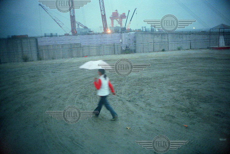 Woman with an umbrella walking past the construction site of the Three Gorges Dam.