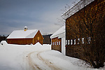 A gravel road passes a shingled barn in Tamworth, NH, USA