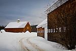 A gravel road passes a shingled barn in Tamworth, NH, USA