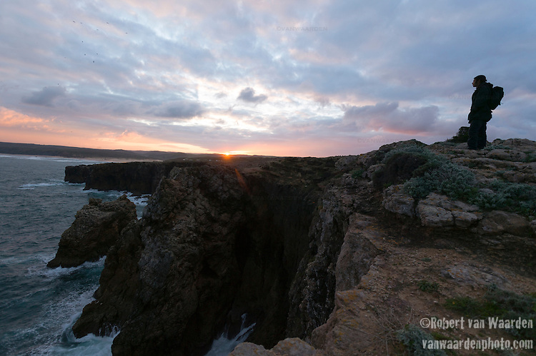 A man watches the sunrise on the cliffs of Bordeira in the Algarve of Portugal.