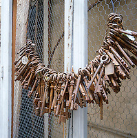 A collection of old rusty keys hangs on a steel ring in front of a pair of doors with wire mesh.