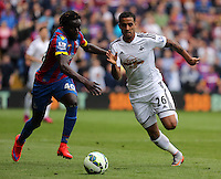 Pictured: Kyle Naughton of Swansea (R) is challenged by Pape Souare of Crystal Palace<br />