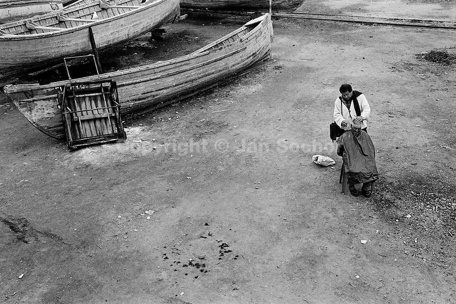 A barber shaving an old fisherman at caleta (a service yard) in the port of Coquimbo, Chile, 3 July 2002.