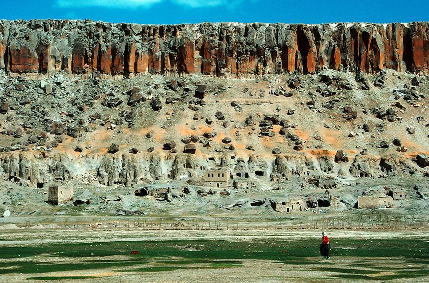 .Turkish girl in red sweater in rocky landscape, near Guzelyurt, central Anatolia, Turkey...