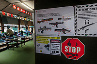 "Switzerland. Canton Ticino. Cureglia is a municipality in the district of Lugano. ""Tiratori del Gaggio"" society. Shooting range.  Rules on how to handle weapons inside the range. The property is monitored by video surveillance. Warning sign. Young shooters' course. The courses, whose organisation is delegated by the Federal Department of Defence, Civil Protection and Sport to the various local shooting societies, are open to young swiss people, boys and girls, from 15 to 20 years old. Girls and boys learn how to handle and fire with the assault rifle SG 550, also called Fass 90, used by the Swiss Army. The SG 550 is an assault rifle manufactured by Swiss Arms AG (formerly Schweizerische Industrie Gesellschaft) of Neuhausen, Switzerland. ""SG"" is an abbreviation for Sturmgewehr, or ""assault rifle"". The rifle is known as the Fass 90 or Stgw 90. An assault rifle is a selective-fire rifle that uses an intermediate cartridge and a detachable magazine. 23.02.2019 © 2023 Didier Ruef"