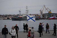 Citizens greeting a Russian military ship ias it enters the port of Sevastopol.