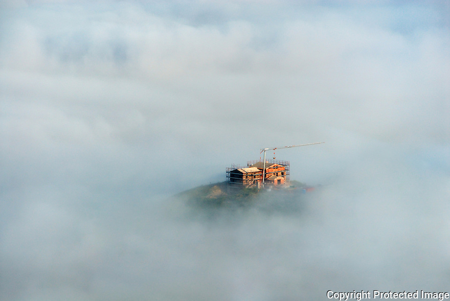 A house being restored on a top coming up though the clouds in Toscana, Italy