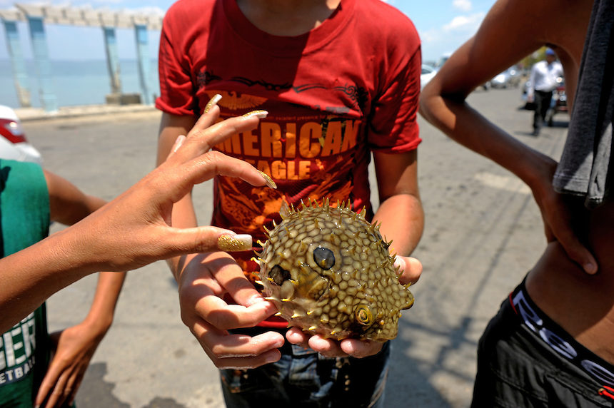 Children display a fish caught by hand in the waters off Punta Gorda in Cienfuegos, Cuba. MARK TAYLOR GALLERY