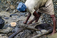 A barefoot Colombian woman miner diggs the goldbearing mud in the river San Juan near Tadó, Chocó dept., Colombia, 28 May 2004. Chocó is a no man's land. The large inaccessible rainforest jungle area in the western lowlands of Colombia is mainly inhabited by Afro Colombian population, descendents of African slaves. High presence of malaria, guerilla drug traffic routes, tropical deseases and only an irregular river transport makes this region virtually lost. Gold that is found in the jungle rivers of Chocó is the only hope for many although they never find what they dream about.