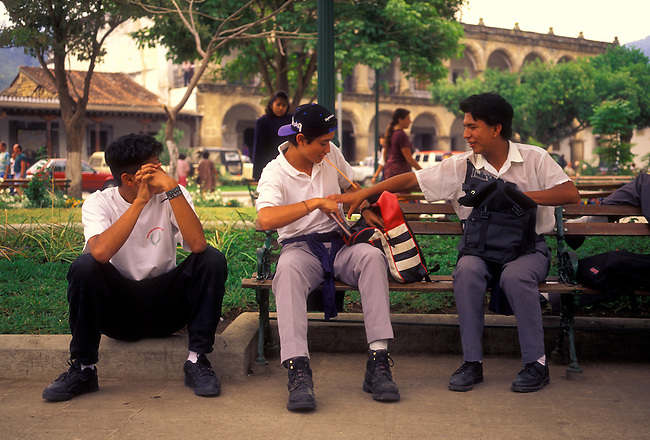 Three male students in Plaza Mayor, Antigua, Sacatepequez Department, Guatemala, Central America