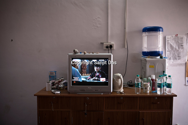 The desk of the 25 year old Chinese interpreter, Li Wez Wez in her dormitory in the Chinese Colony of the Adani Power Plant in Mundra port industrial city of Gujarat, India. Indian power companies have handed out dozens of major contracts to Chinese firms since 2008. Adani Power Ltd have built elaborate Chinatowns to accommodate Chinese workers, complete with Chinese chefs, ping pong tables and Chinese television. Chinese companies now supply equipment for about 25% of the 80,000 megawatts in new capacity.