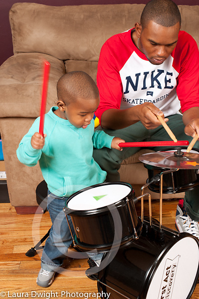 Two year old toddler boy at home with father playing music using drum set