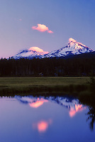 Sunrise on Three Sisters Mountains, and pond. Oregon.