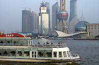 Tourists on a cruise boat on the Huangpu River in Shanghai, China,  with the skyscrapers of the Pudong Financial District behind..08 Nov 2004