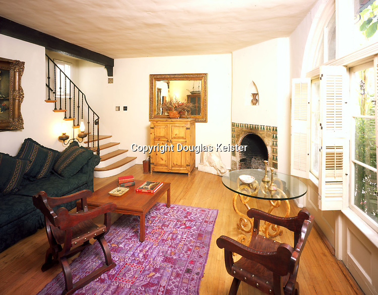 The unpretentious apartment interiors at Patio del Moro demonstrate the Zwebell's overriding concern with livability.  The tiled, horseshoe-arched fireplace is the focal point of this simple living room, and forms its only overtly decorative feature. The hardwood floor, stair rail, and ceiling beam are all quite plainly detailed for the period.  In place of pretense, the Zwebells gave the room a generous view of the lush courtyard through the broad, round-arched window at right.  The upstairs bedroom features a small balcony with an equally tranquil prospect.