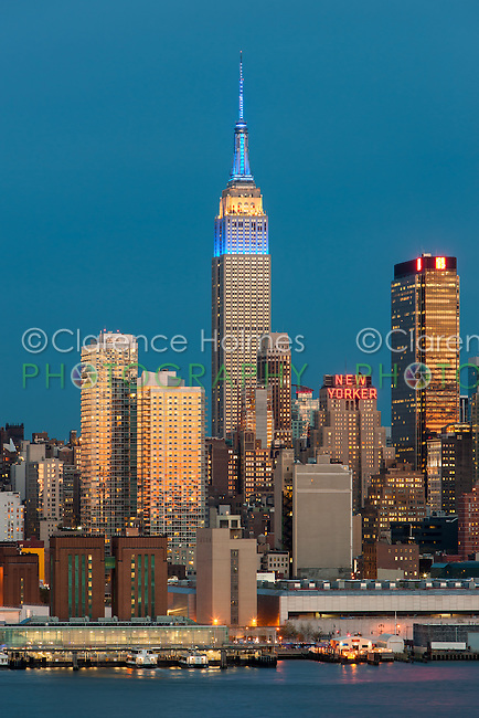 The Empire State Building and Manhattan skyline at twilight, with the orange glow of the western sky reflected in the windows of the buildings.  The Empire State Building was illuminated in Blue/Yellow/Blue lights in honor of Europe Day.