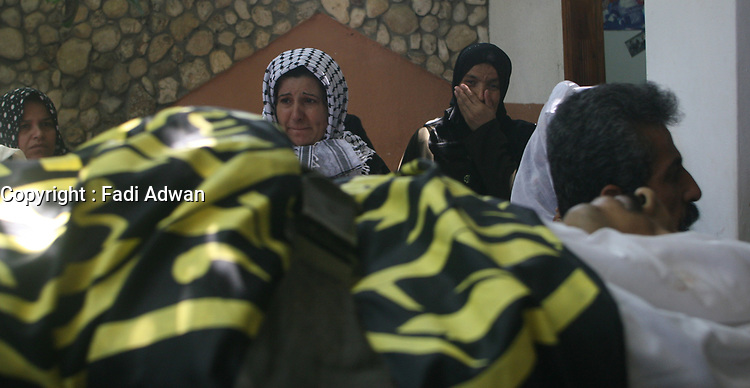 """Palestinian women look on as mourners pass by carrying the body of 25-year-old Hisham al-Jamal during his funeral at Rafah refugee camp in the Gaza Strip, 05 August 2007. Two Palestinian militants from the Islamic Jihad group were killed yesterday and others wounded in an Israeli air strike targeting a car in the south of the Gaza Strip, medical sources said.""""photo by7 Fady Adwan"""""""