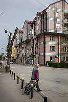 Serbia. Vranje is a city and the administrative center of the Pčinja District in southern Serbia. Town center. Architecture. Facades' buildings painted with Burberry's brand designs. An elderly woman crosses the street and pulls a pushcart filled with firewood. 17.4.2018 © 2018 Didier Ruef for the Pestalozzi Children's Foundation