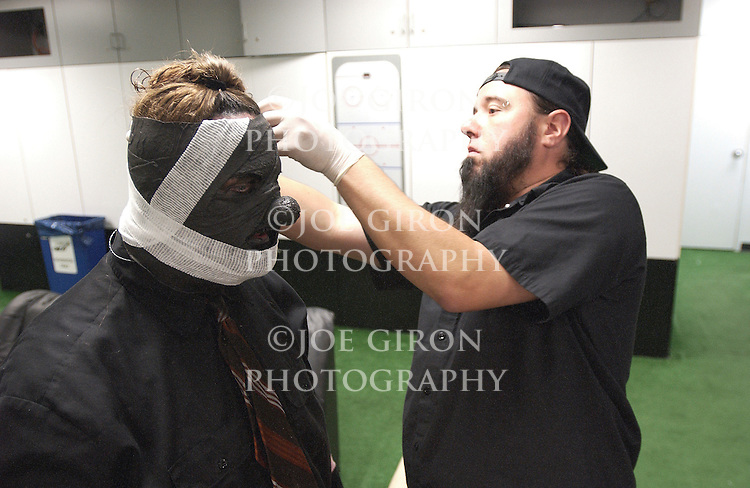 Tongs applies bandages & fake blood to the Clown's stage mask.
