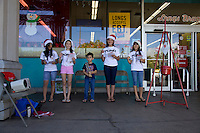 Five local youth wearing Santa hats sing Christmas carols for the Salvation Army outside of Longs Drugs store in Kahalui, Maui.