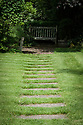 Paving slabs in lawn leading to wooden seat, Vann House and Garden, Surrey, mid June.