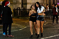 Two young women in Wind Street, Swansea, Wales  on Mad Friday, Booze Black Friday or Black Eye Friday, the last Friday night before Christmas Day, when traditionally people in the UK go out to celebrate the start of their holidays. Friday 22 December 2017