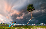 Beach visitors scramble toward their car as a storm front moves over Shell Point Beach on a July afternoon.