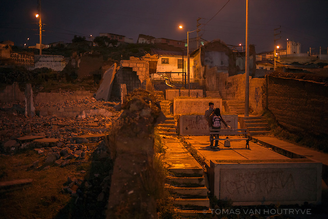 Two teenagers stand among abandoned and wrecked buildings in the Pilar neighborhood of Cerro de Pasco, Peru. The previously bustling neighborhood has been transformed into a wasteland after being purchased by the Volcan mining company for expansion of the adjoining open-pit mine.